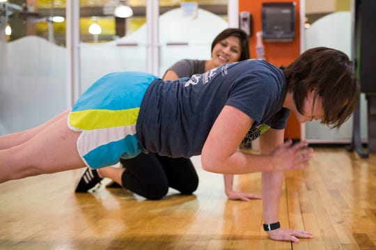 Deonna Walker leads News Sentinel reporter Maggie Jones in a set of planks with shoulder taps, which strengthens core and shoulder muscles.