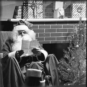 E-G Photographer Duke Ellis caught Santa in his house on Fountain Square in Dec. 1970 reading one of the many letters he had received. This photo is from the Duke Ellis Collection of the Fairfield County Heritage Association.