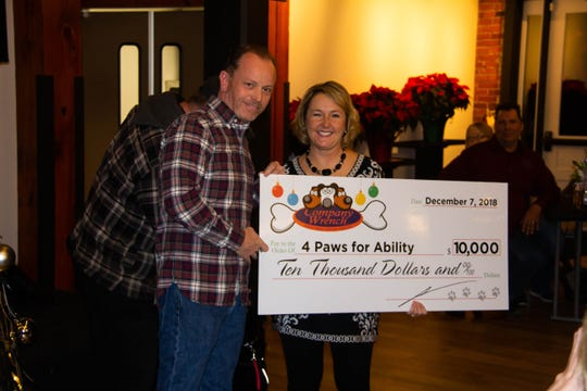Brad Hutchinson and Kelly Camm. Company Wrench donates $10,000 to 4 Paws for Ability.