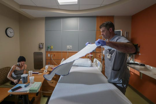 Bart Conley changes the bed linens in the room of April Cobb at Norton Children's Hospital.