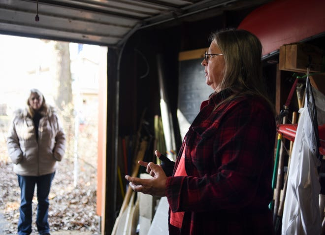 Lansing resident Barb Barton talks with fellow volunteers in her garage on December 19, 2018. Barton uses the garage as a home base for organizing bottled water drives for Flint.