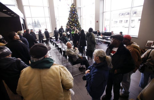 BWL customers wait in line at the customer service walk-in center BWL set up in the REO Town headquarters Monday, December 30, 2013, for some of the 1,100 customers still without power since last week's ice storm.  [Photo December 30, 2013]