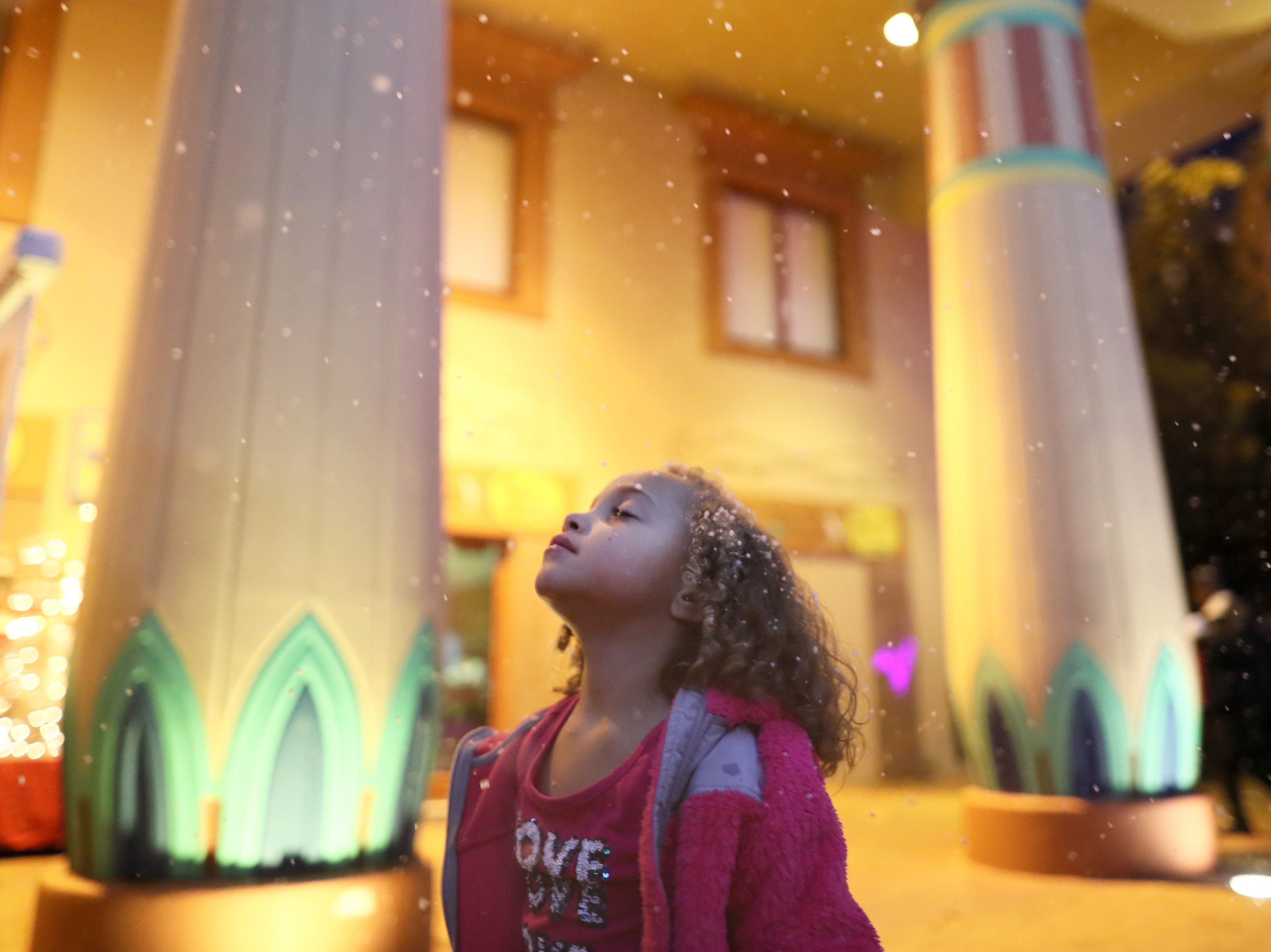 Chloe Conley, 5, holds her face up under the artificial snowflakes greeting guests of Zoo Lights, a holiday season event at the Memphis Zoo Saturday, Nov. 24, 2018.
