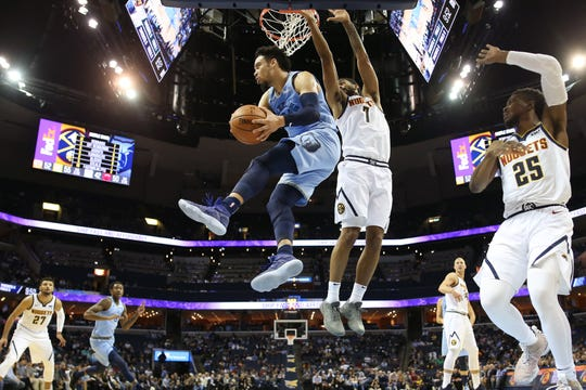 Memphis Grizzlies guard Dillon Brooks looks to pass the ball from the air, as Denver Nuggets forward Trey Lyles defends during their game at the FedExForum on Wednesday, November 7, 2018.