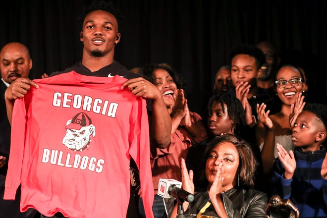 December 19 2018 - Nakobe Dean, the top-ranked inside linebacker in the country and the No. 14 overall prospect in the country according to the 247Sports composite rankings, holds up a Georgia Bulldogs shirt after committing to the school doing an announcement on Wednesday at Horn Lake High School.