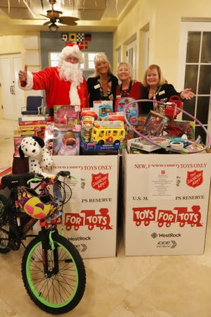 The Marco Island Yacht Club collected Toys for Tots at its Holiday Party. Santa was on hand to thank everyone who donated. With Santa are the Yacht Club members who coordinated the drive, from left: Dwyn Von Bereghy, Vicki Bretthauer and Angela Holt.