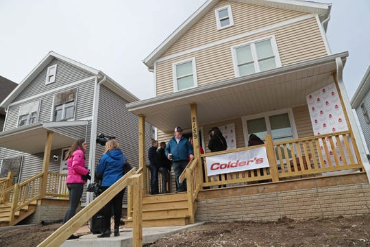 People gather at Sade's new Habitat for Humanity home.