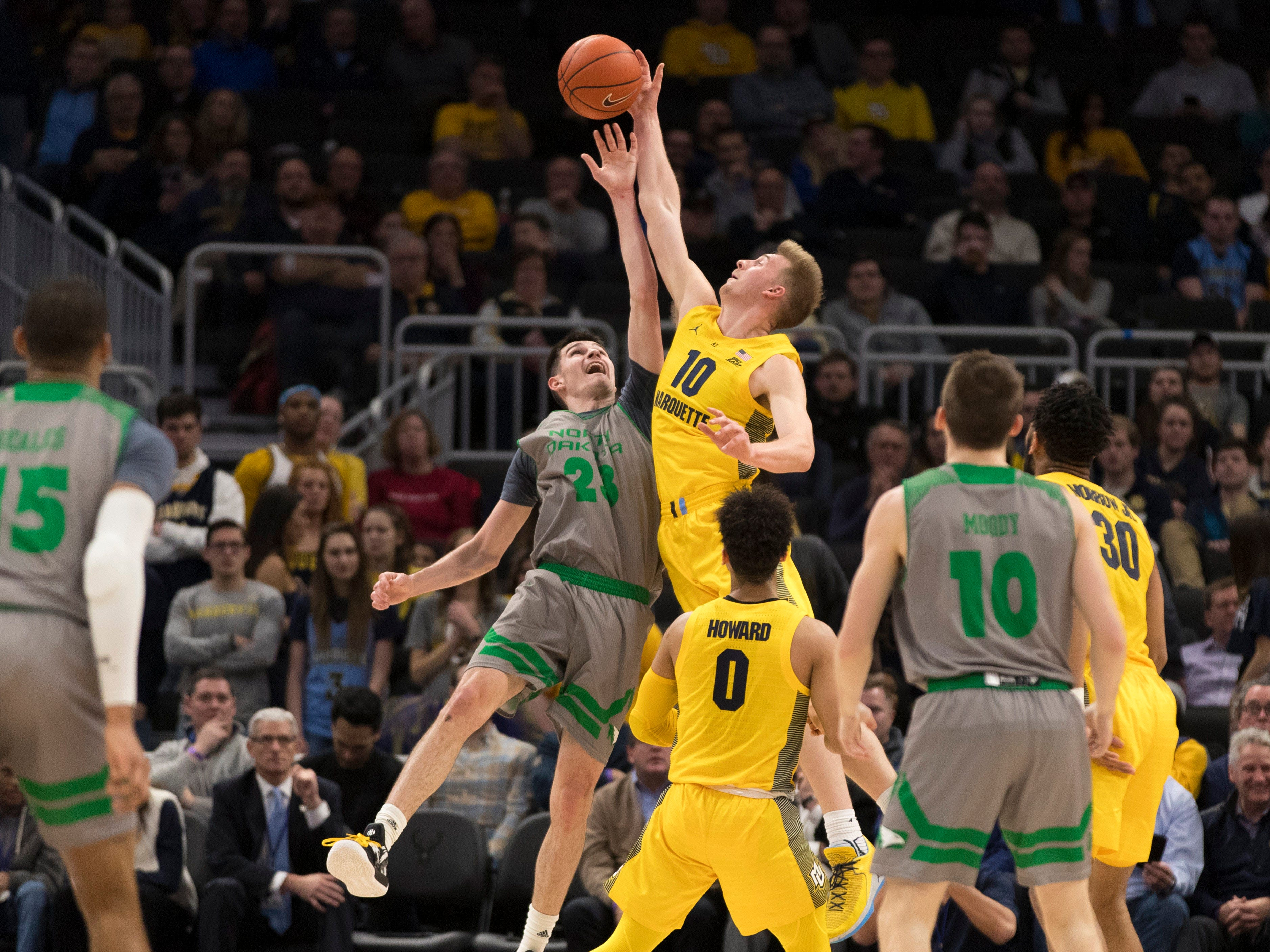 Sam Hauser (10) of Marquette reaches for a rebound in a battle with North Dakota's Kienan Walter on Tuesday night.