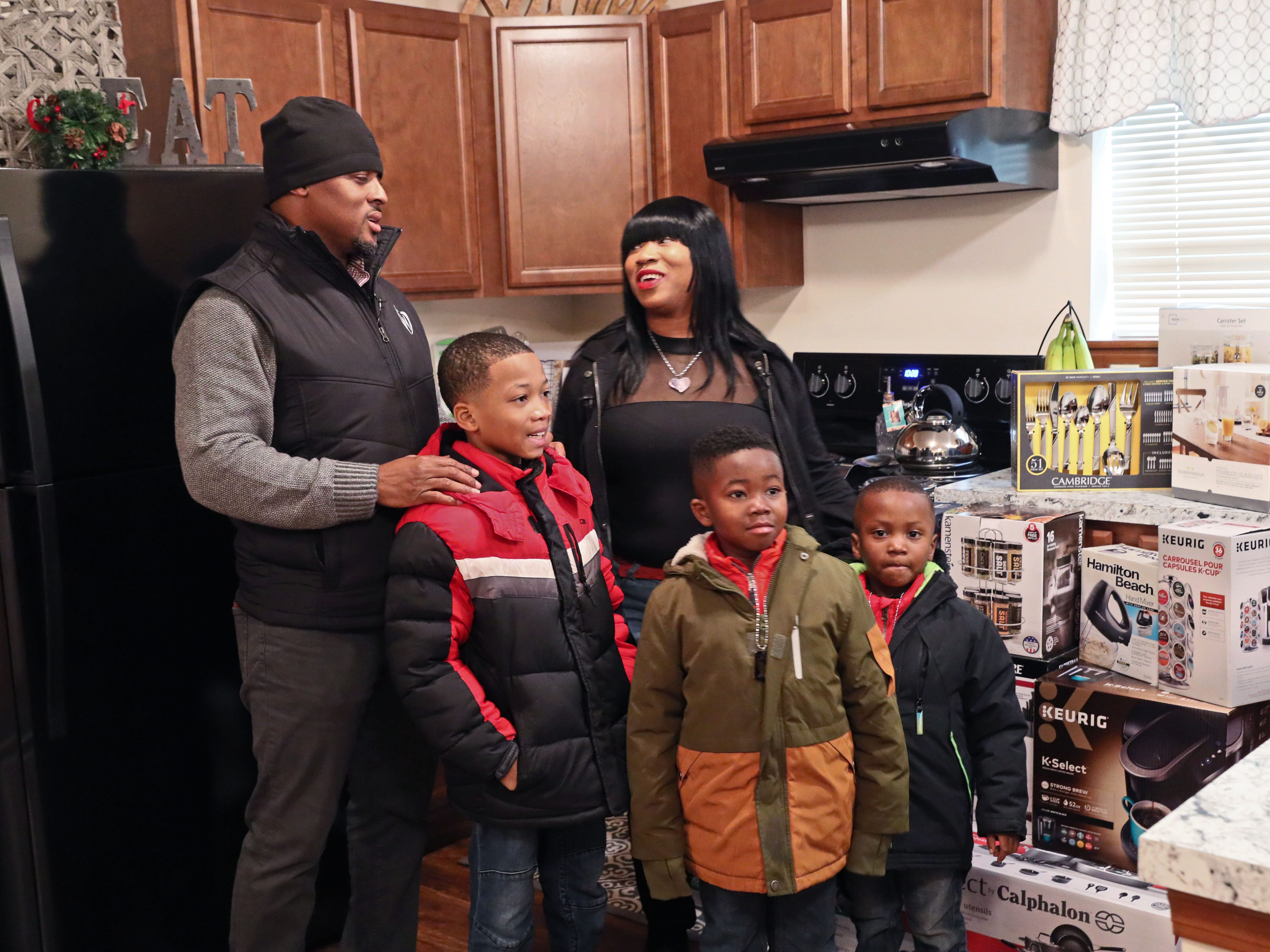 Warrick Dunn and Sade and her children tour the kitchen.