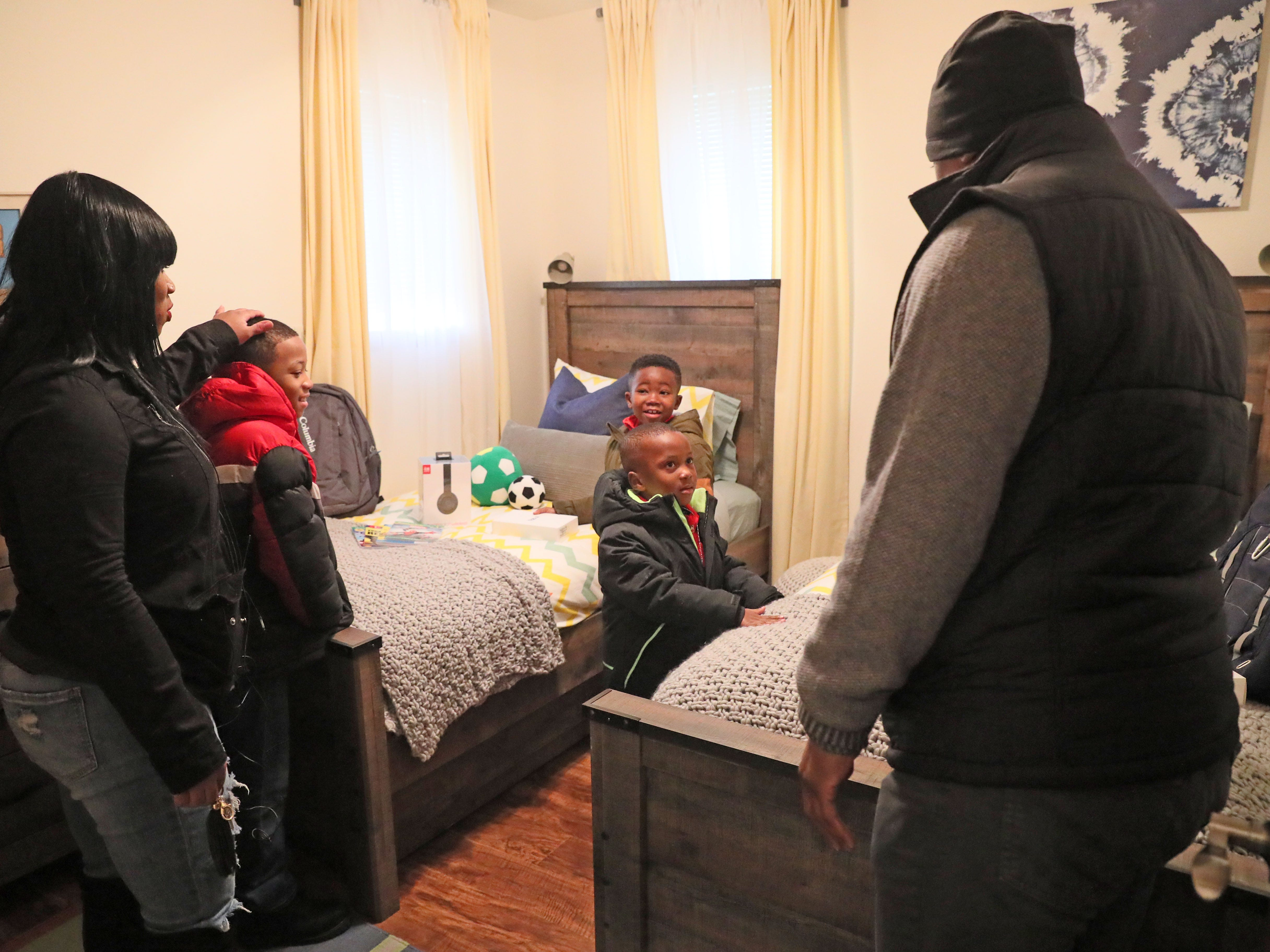 Sade (from left), her sons Demarion,  Robert and Samir and Warrick Dunn, look over one of the children's bedrooms.