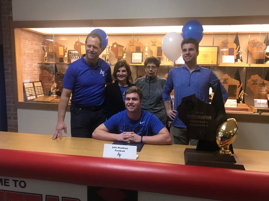 Homestead senior Jake Raddatz poses with family and the Division 2 state championship trophy after signing to play football at Air Force on Wednesday.