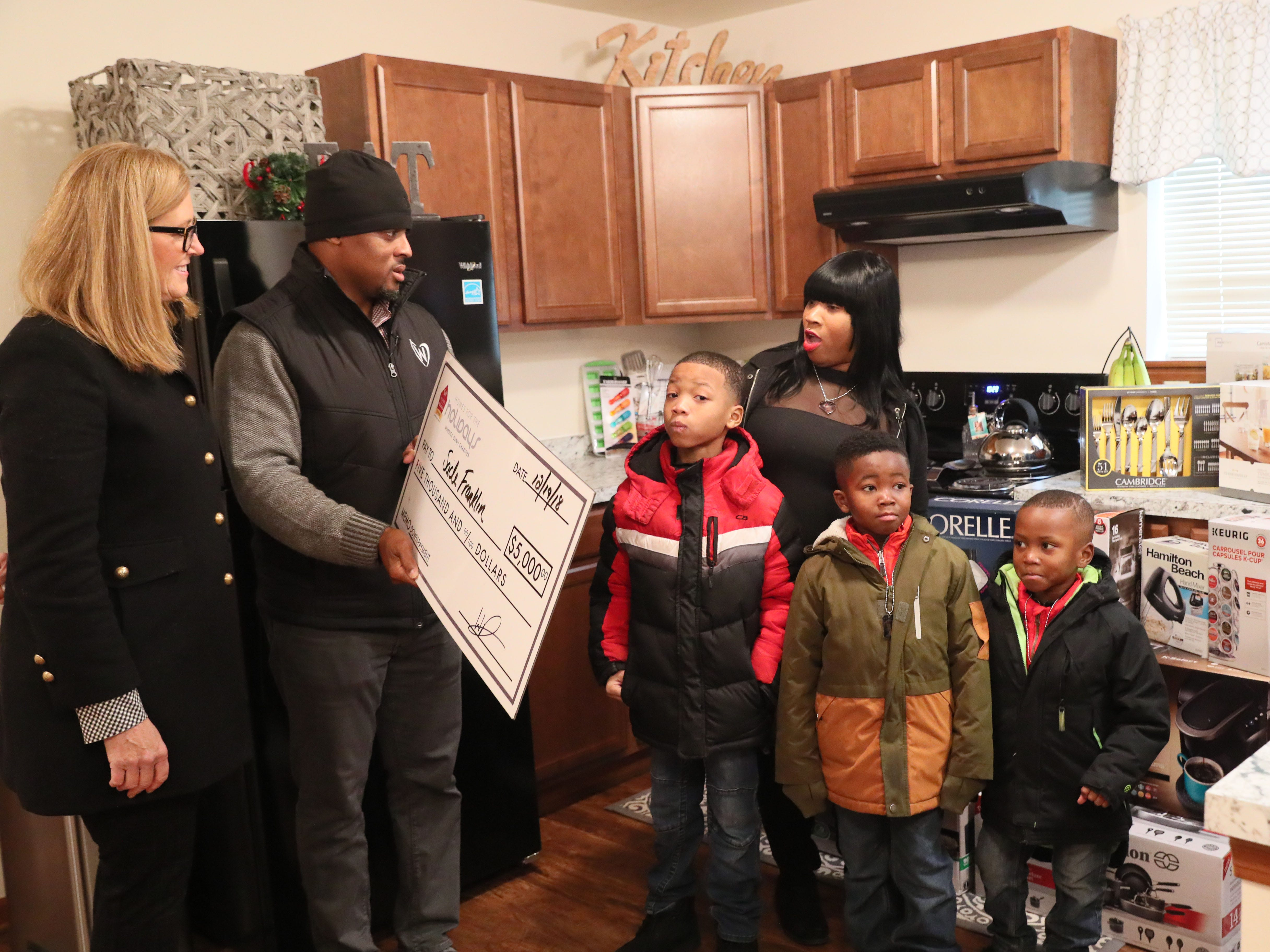 Warrick Dunn hands Sade and her children a check for $5,000 to be put toward their down payment. The check is from Keller Williams Realty in Milwaukee, which was represented by Maureen Stalle (left).