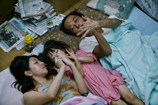 """Ando Sakura (from left), Sasaki Miyu and Lily Franky share a moment as part of an unlikely family in """"Shoplifters."""""""