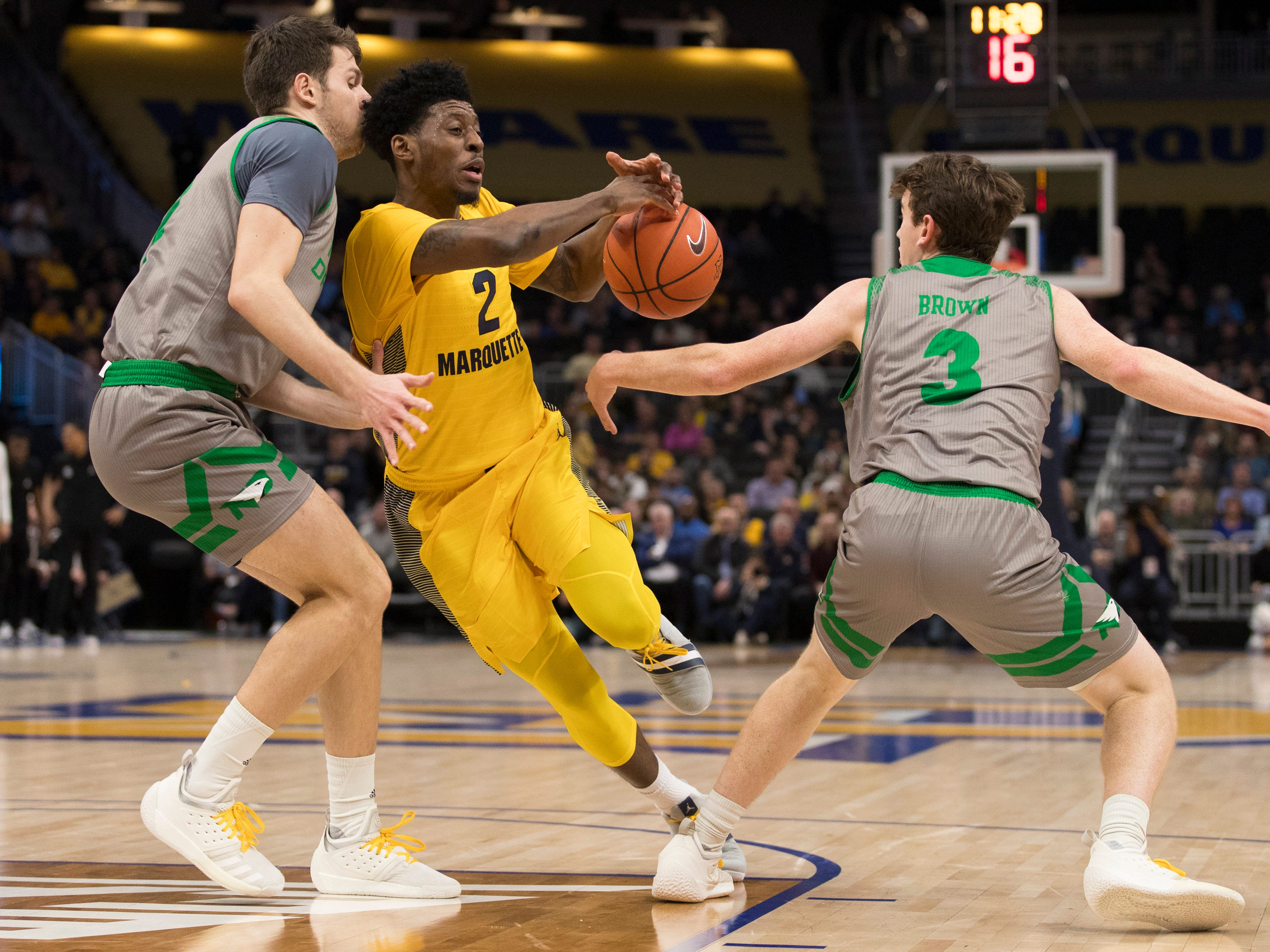 Billy Brown (right) of North Dakota knocks the ball away from a driving Sacar Anim of Marquette during the first half.