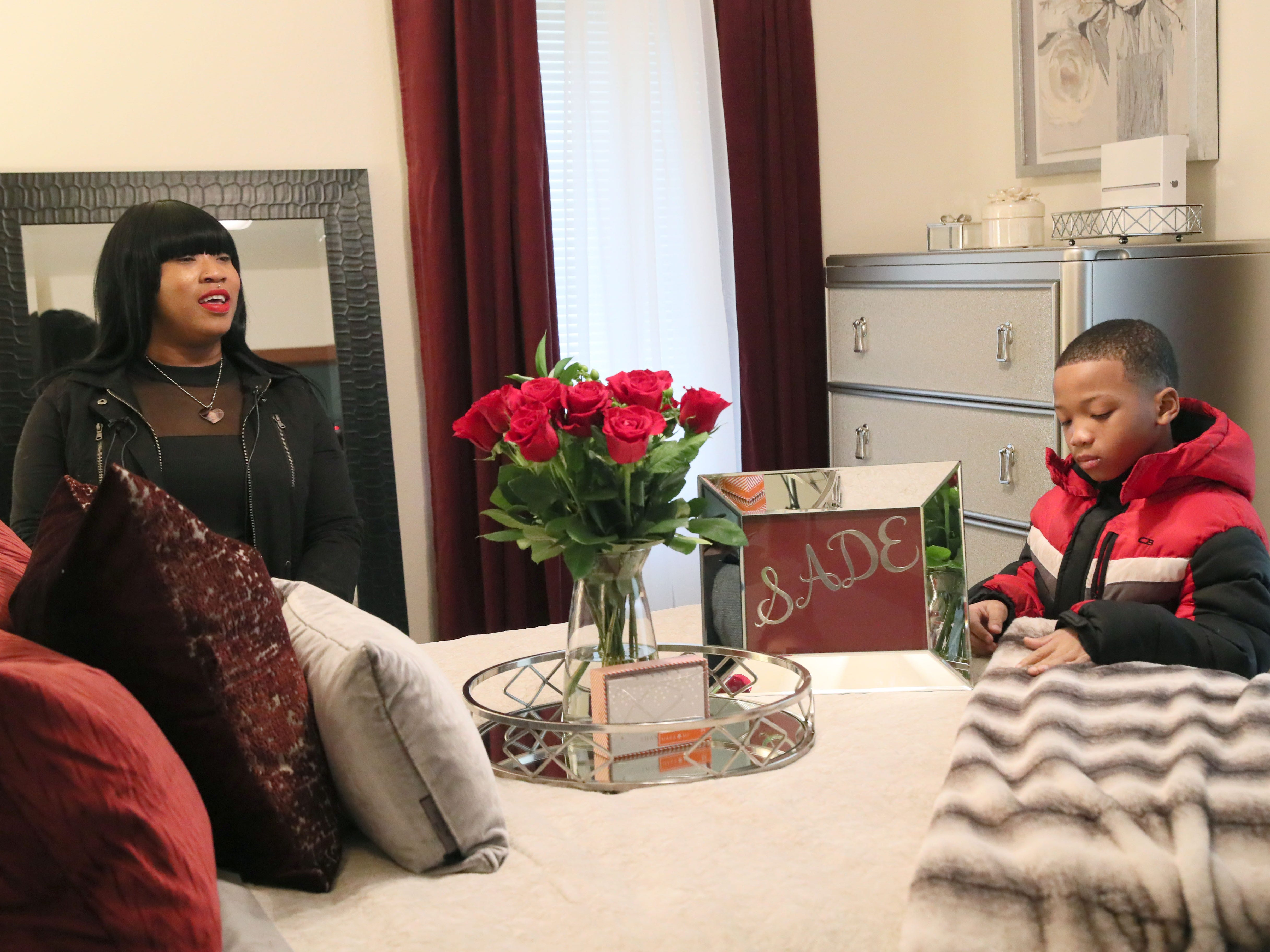 Sade looks over the master bedroom with her son Demarion.