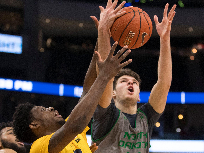 Sacar Anim of Marquette battles Filip Rebraca of North Dakota for a rebound on Tuesday night.