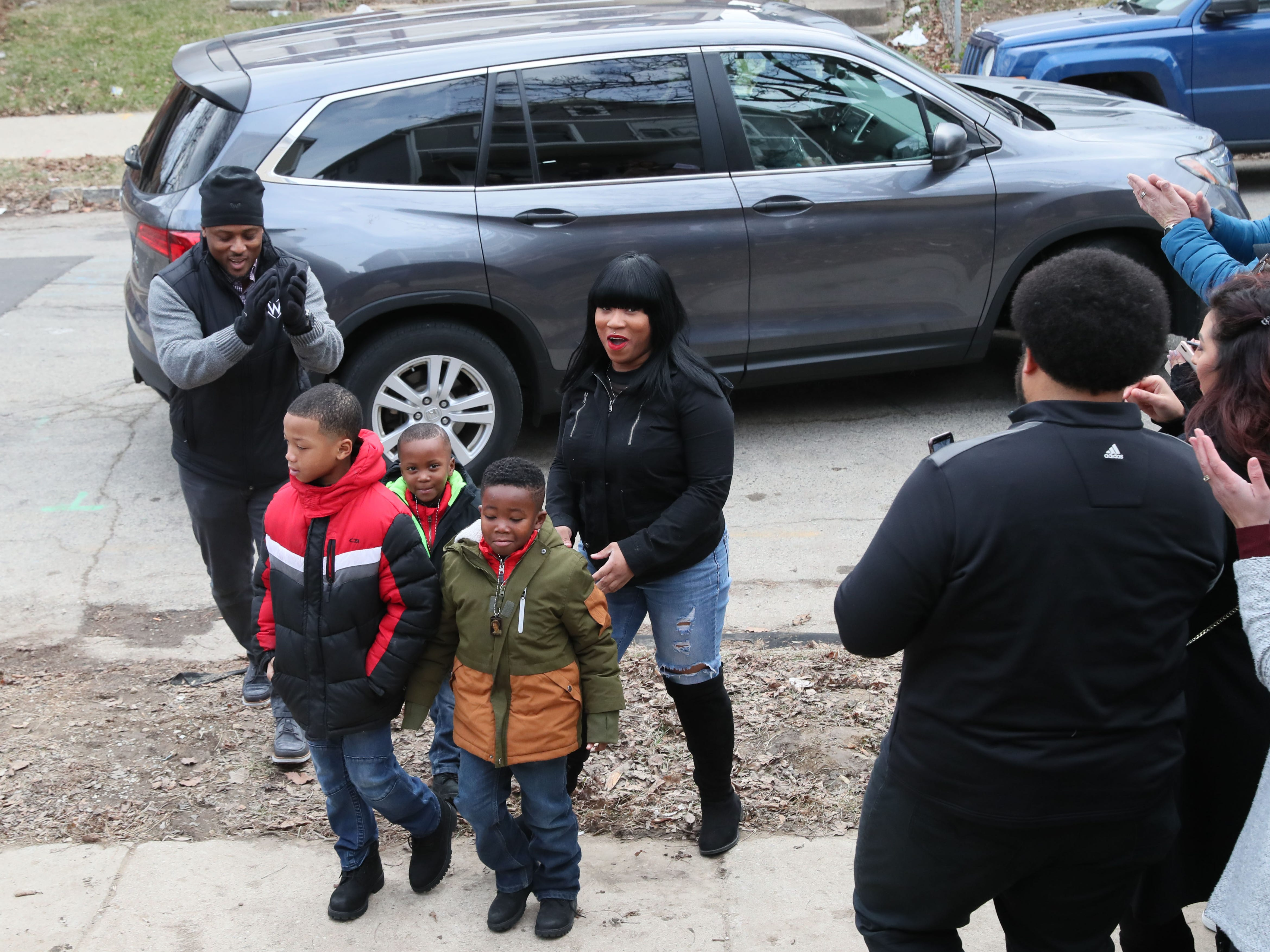 Warrick Dunn, meets Sade and her children Demarion (from left), Samir and Robert as those on hand applaud their arrival in front of the house.