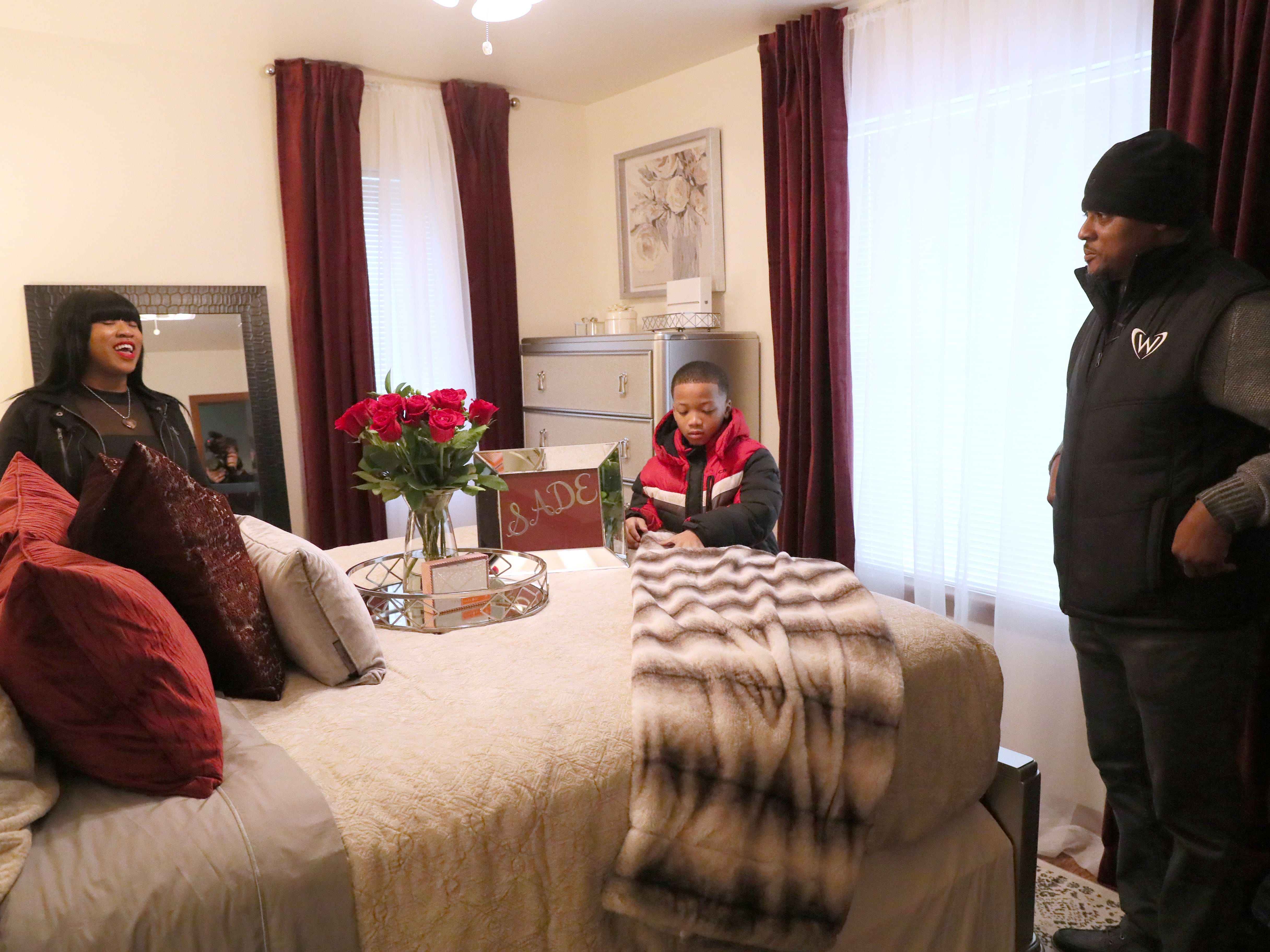 Sade and her son Demarion look over the master bedroom while  Warrick Dunn looks on.