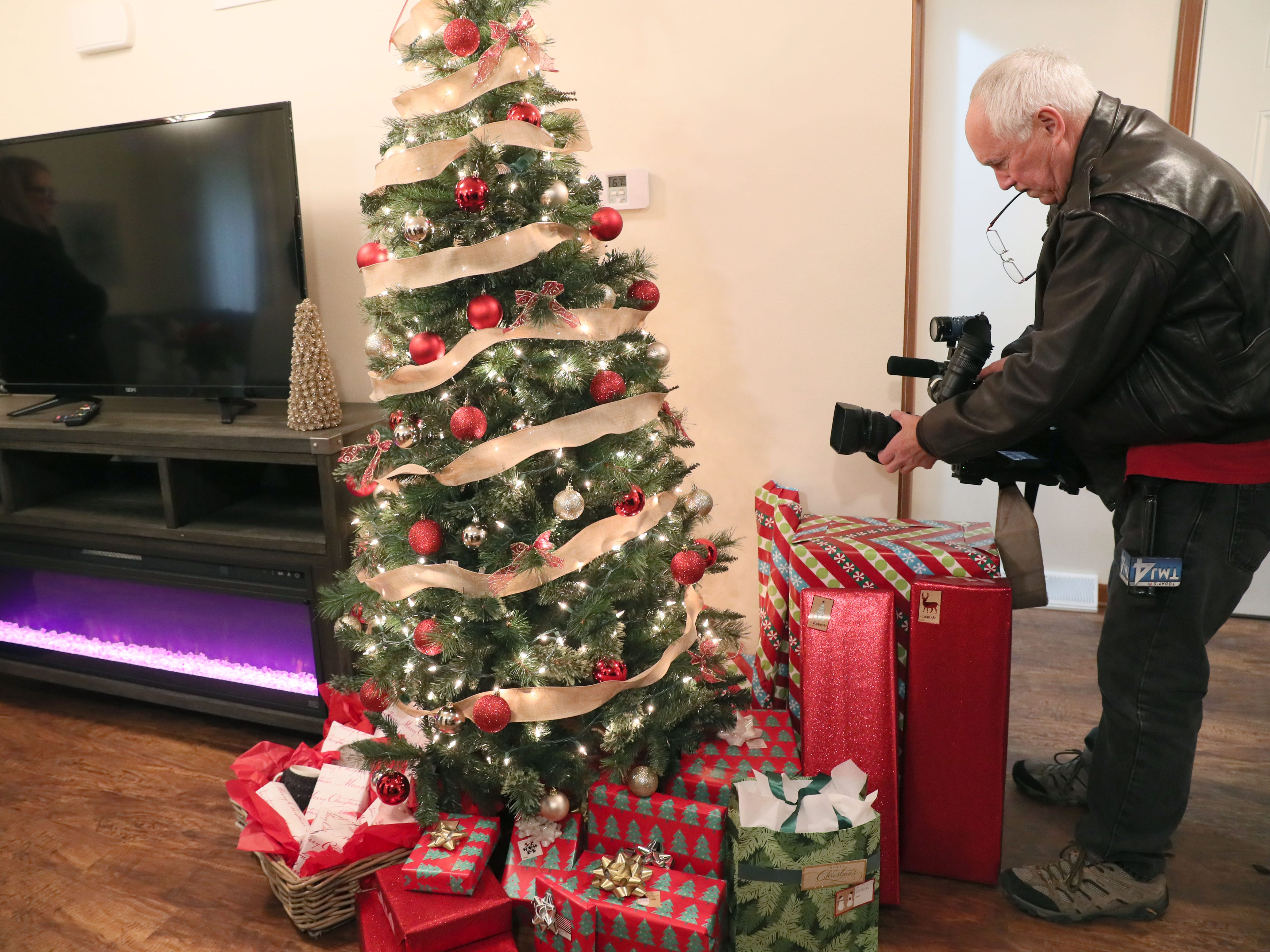 A news photographer takes images of the Christmas tree.