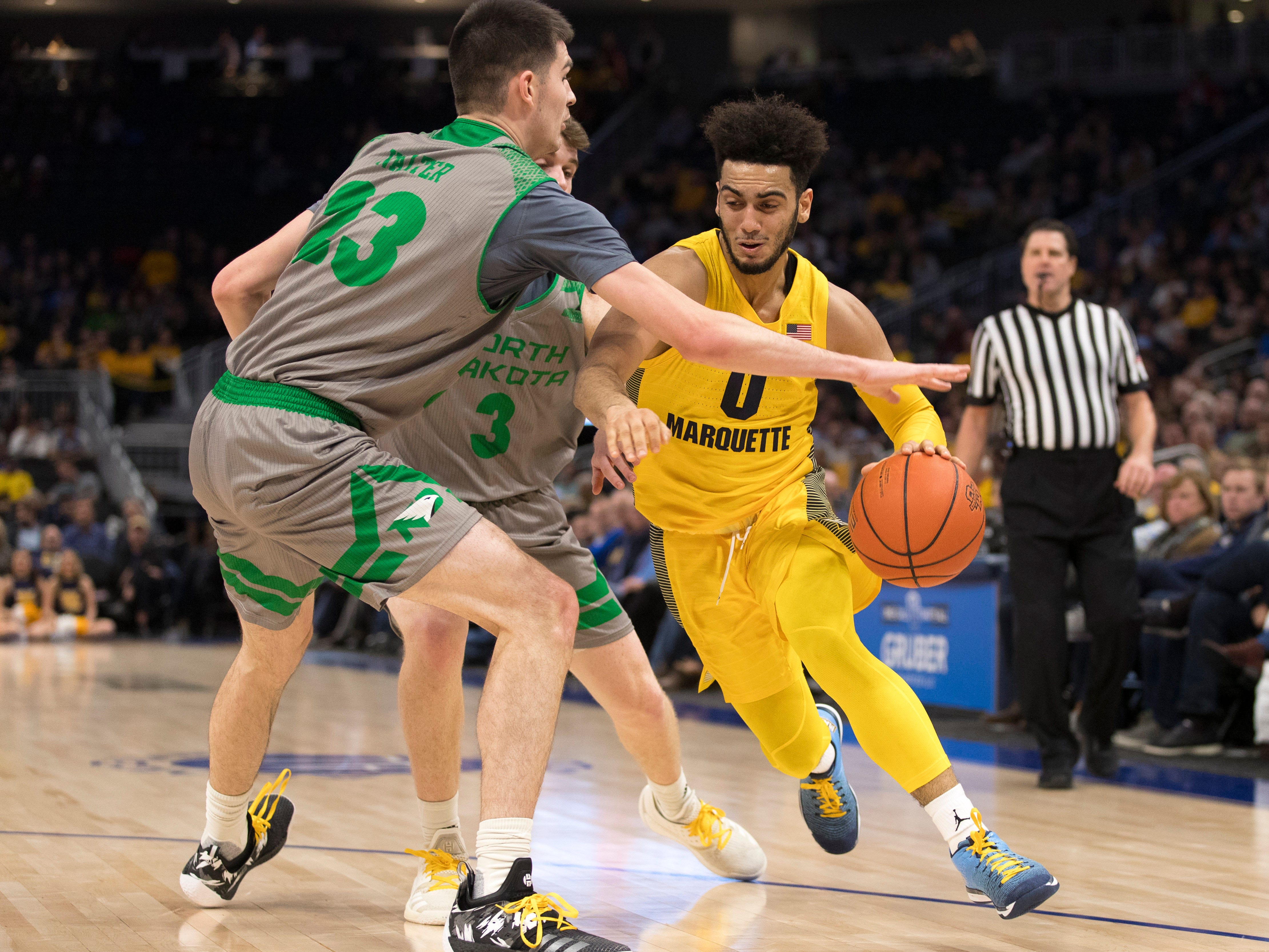 Golden Eagles guard Markus Howard drives for the basket against Fighting Hawks forward Kienan Walter (23) and Billy Brown during the first half.