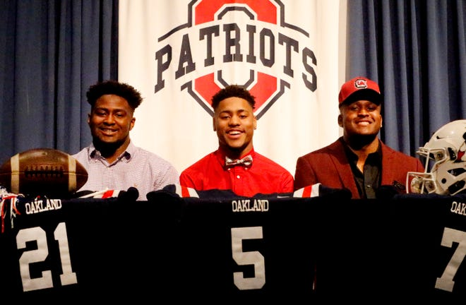 Oakland football players, from left, Christian Cantrell (Tennessee Tech), Woodi Washington (Oklahoma) and Joseph Anderson (South Carolina) all signed on the first day of the early signing period Wednesday.