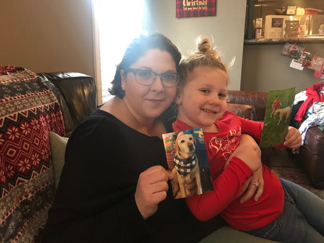 "Aly Duke and Preslyn pose with photos of their missing dog, Marley. The yellow Labrador was last seen Tuesday night. He was wearing a black and white checkered bandana with the words ""ho ho ho"" and a collar with tags. He also is microchipped."