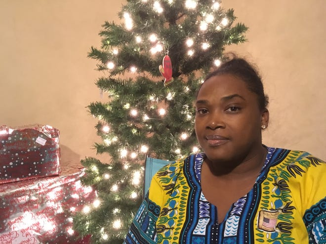 Shantay Peairs poses Tuesday by her family Christmas tree at her Smyrna home. She recently filed a complaint accusing a Smyrna police officer of racially profiling her 13-year-old son while the boy was walking home in her neighborhood after playing basketball with friends.