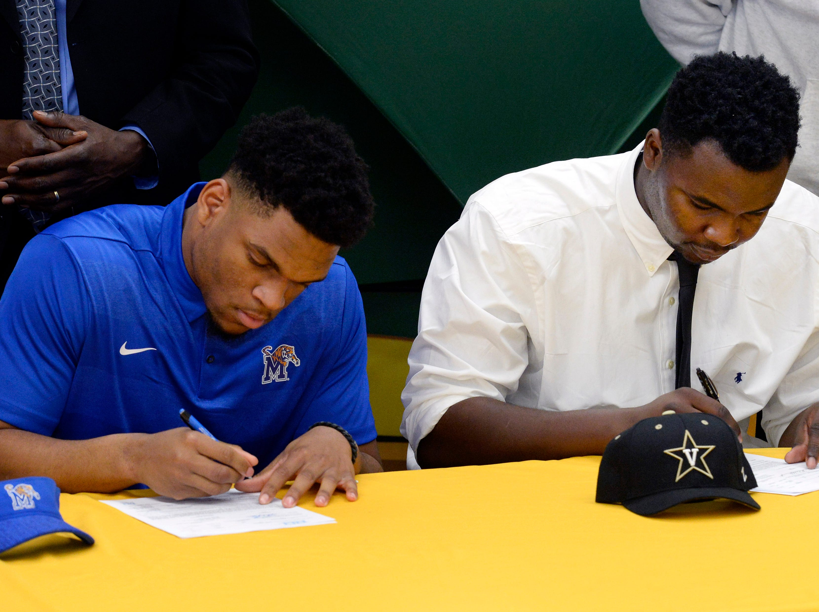 Hillsboro High School's Joe Honeysucker, left,  and Donald Fitzgerald sign their national letters of intent to play football in college on Wednesday, Dec. 19, 2018, in Nashville,Tenn. Honeysucker is signing to play for Memphis. Fitzgerald, who played one season of high school football, is the adopted son of Hillsboro Coach Maurice Fitzgerald and is from Nigeria. He is playing for Vanderbilt.