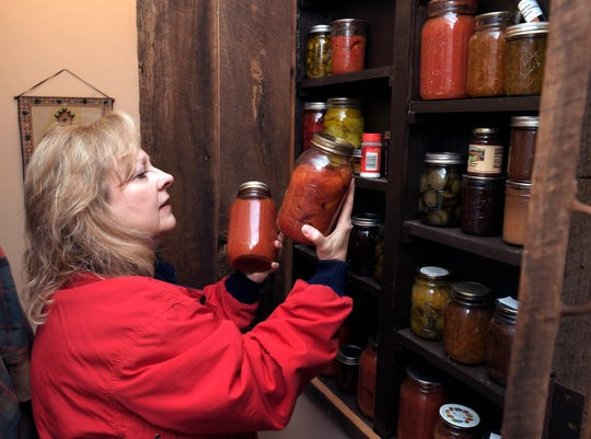 "Leigh Funderburk looks at her canned vegetable cabinet on her Franklin farm. ""I can all my vegetables so we eat out of the freezer all year ... It's a lot less expensive overall than to buy from the grocery store,"" she said."
