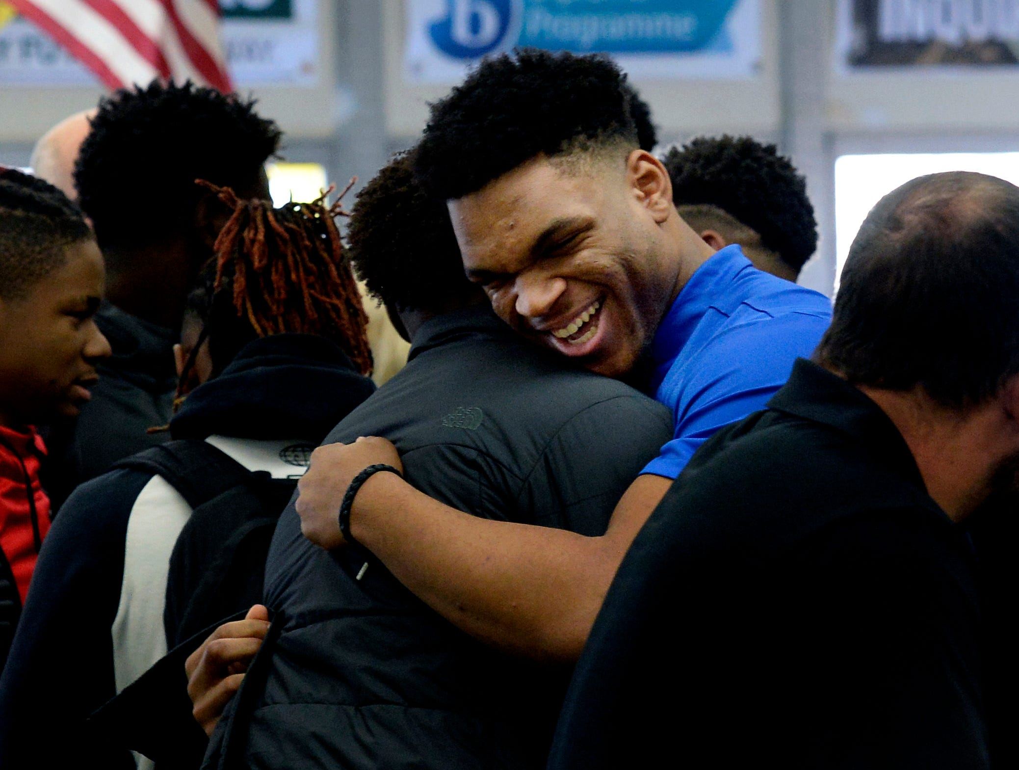 Hillsboro High School football player Joe Honeysucker is greeted before signing his national letter of intent to play football in college on Wednesday, Dec. 19, 2018, in Nashville,Tenn. Honeysucker is signing to play for Memphis. Teammate Donald Fitzgerald, who played one season of high school football, is the adopted son of Hillsboro Coach Maurice Fitzgerald and is from Nigeria. He is playing for Vanderbilt.