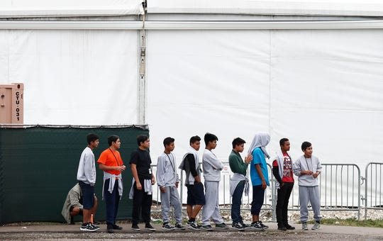 Migrant teens walk in a line at the Homestead Temporary Shelter for Unaccompanied Children, a former Job Corps site that now houses them, in Homestead, Fla., on Monday, Dec. 10, 2018. On sprawling country ranches and busy city centers, in suburban homes and huge crowded tents, the Trump administration has scattered about 14,300 migrant children across the country in a vast network of 150 shelters, detention centers and foster homes over the last 20 months. (AP Photo/Brynn Anderson)
