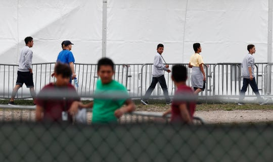 Migrant teens and a staff member walk in a line at the Homestead Temporary Shelter for Unaccompanied Children, a former Job Corps site that now houses them, in Homestead, Fla., on Monday, Dec. 10, 2018. (AP Photo/Brynn Anderson)