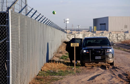 A private security guard throws a soccer ball back inside the Tornillo detention camp for migrant teens in Tornillo, Texas, Thursday, Dec. 13, 2018. The Trump administration announced in June 2018 that it would open the temporary shelter for up to 360 migrant children in this isolated corner of the Texas desert. Six months later, the facility has expanded into a detention camp holding thousands of teenagers. (AP Photo/Andres Leighton)