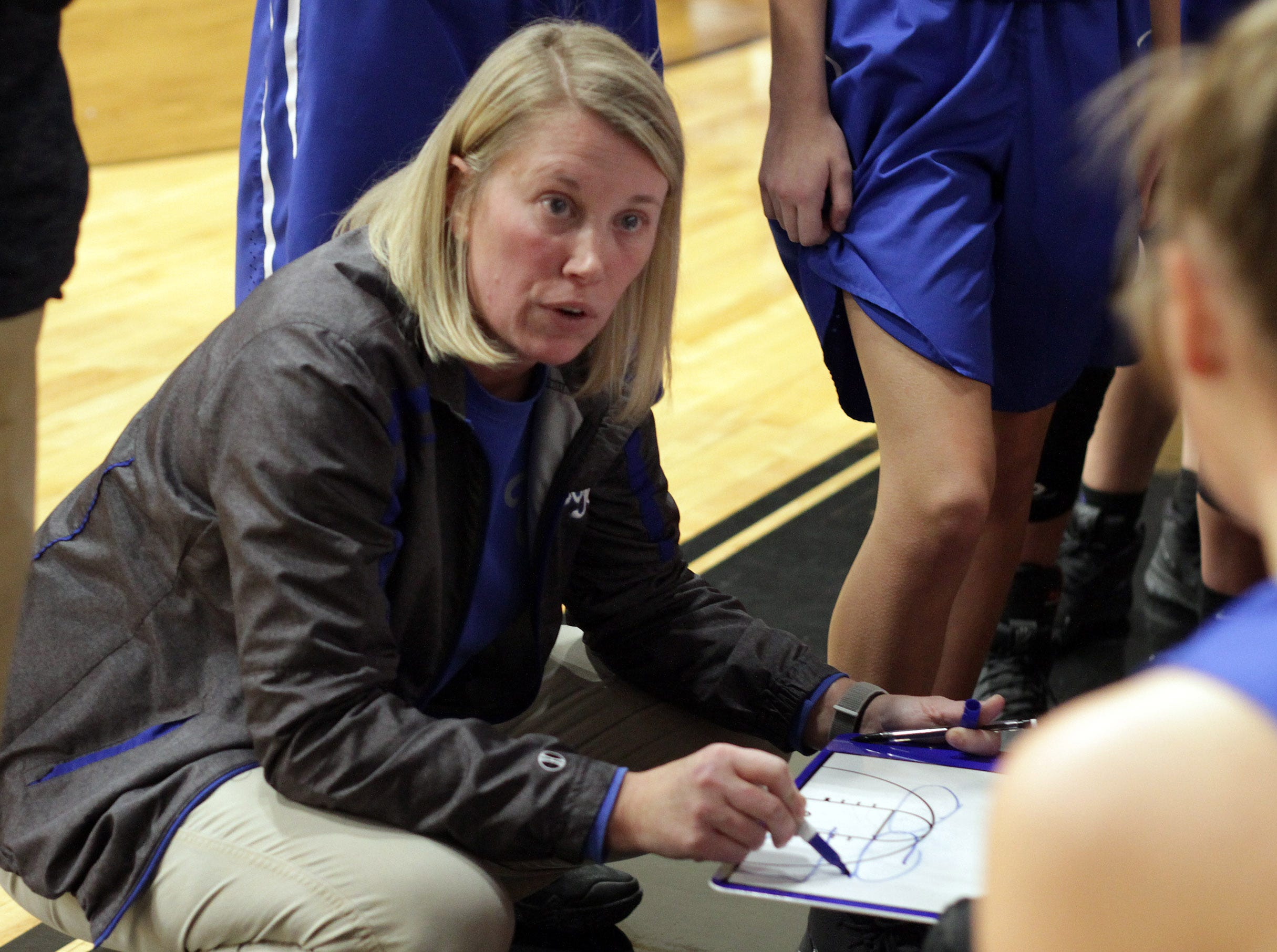 White House coach Kelly Smelcer goes over a play as they play Springfield on Tuesday, December 18, 2018