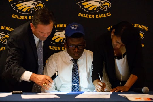 Naples High School offensive tackle Dorian Hinton and his mother Zoralle Walker sign the National Letter of Intent at the school auditorium during the early signing period Wednesday. Hinton will be attending Middle Tennessee State University next year.