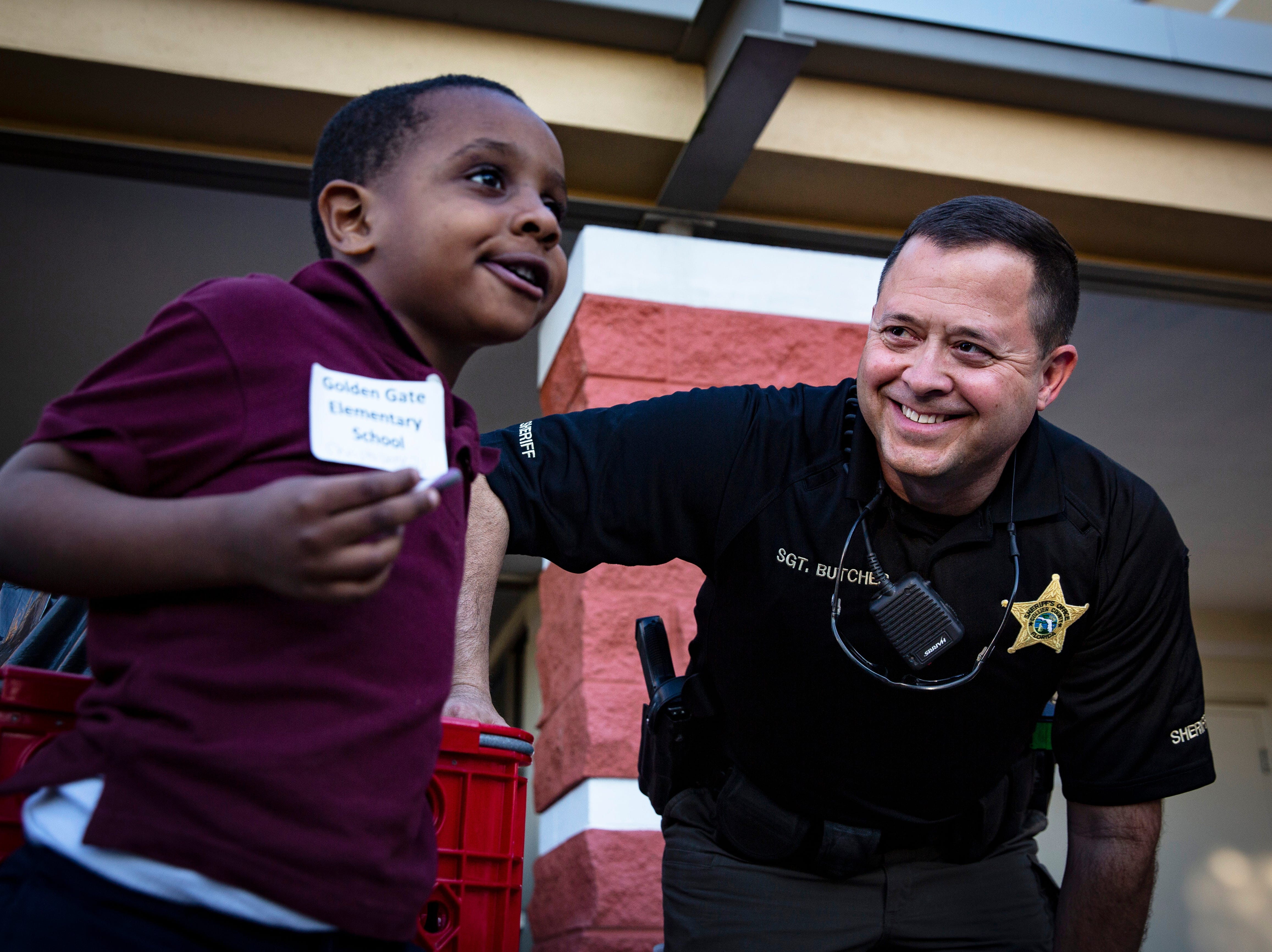 "Sergent Mike Butcher makes conversation with Christopher Dimanche while waiting in line to check out during the ""Shop With a Sheriff"" event at Target in North Naples on Tuesday, December 18, 2018. The Jewish Federation of Greater Naples partnered with the Collier County Sheriff's Office for the fourth year in a row to help 78 children and their families during the holiday season."