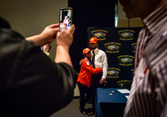 "Cesare ""Chez"" Mellusi smiles with his mother, Thyrza Mathis, at the end of the early signing period Wednesday, Dec. 19, 2018, at Naples High School. The running back for the Golden Eagles' state finals team will be attending Clemson University in South Carolina on a football scholarship."