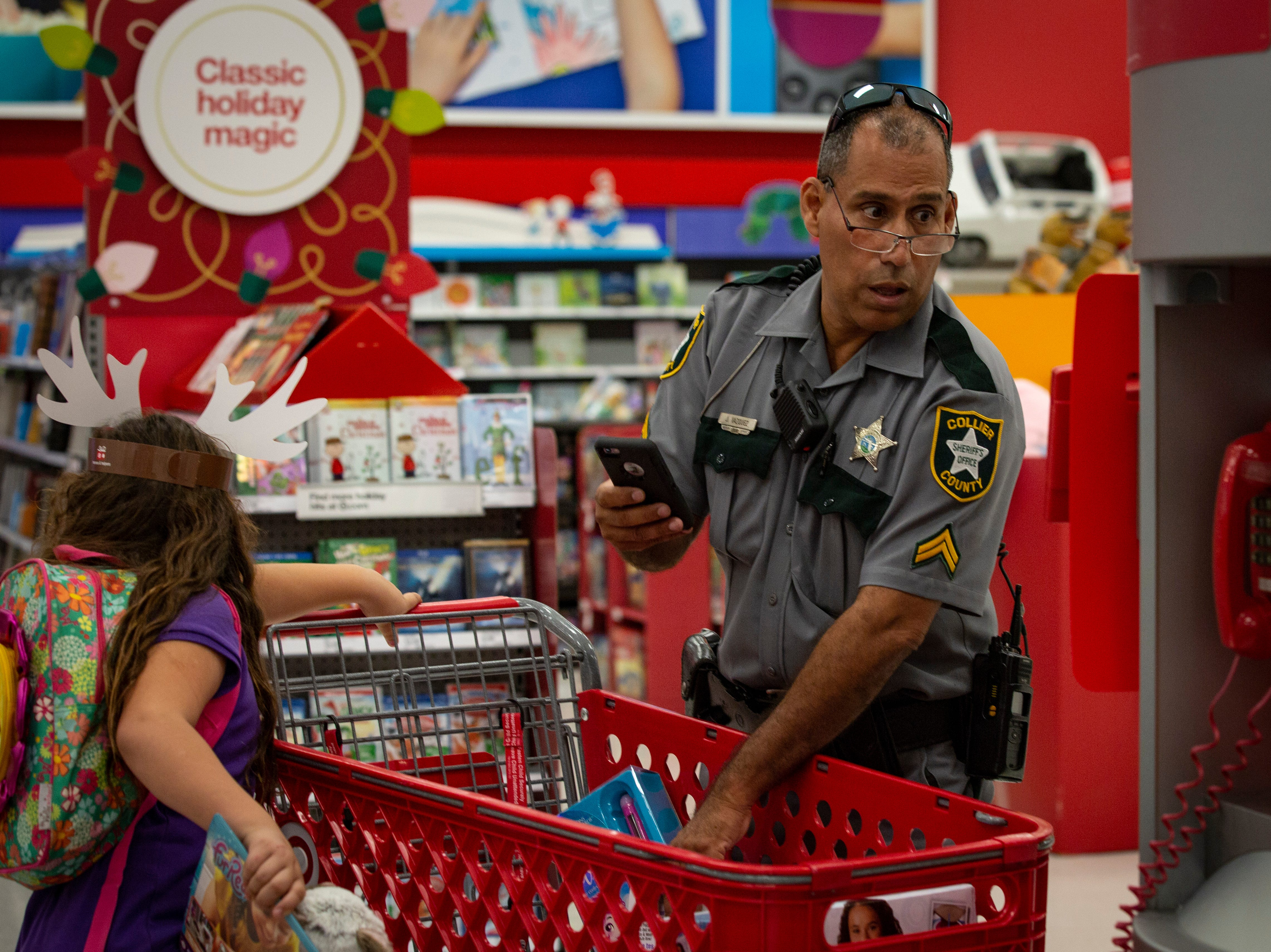Officer Juan Vazquez looks over at the barcode scanner unable to get his calculates right during the ÒShop With a SheriffÓ event at Target in North Naples on Tuesday, December 18, 2018. The Jewish Federation of Greater Naples partnered with the Collier County SheriffÕs Office for the fourth year in a row to help 78 children and their families during the holiday season.