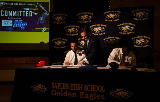 Naples High School football players Chez Mellusi, left and Dorian Hinton, right, sign the National Letter of Intent, while head football coach Bill Kramer assists them at the school auditorium on Wednesday.