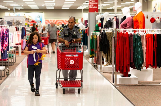 Bella Edwards and officer Juan Vazquez spend time talking as they walk towards the cash register during the ÒShop With a SheriffÓ event at Target in North Naples on Tuesday, December 18, 2018. The Jewish Federation of Greater Naples partnered with the Collier County SheriffÕs Office for the fourth year in a row to help 78 children and their families during the holiday season.