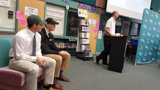 Gulf Coast High School football players Adam Masterson (left) and Luke Baker listen as athletic director Matt Kuk (right) introduce them at National Signing Day. Masterson, a safety, committed to Stetson, while Baker, a tight end, signed with Southern Miss.