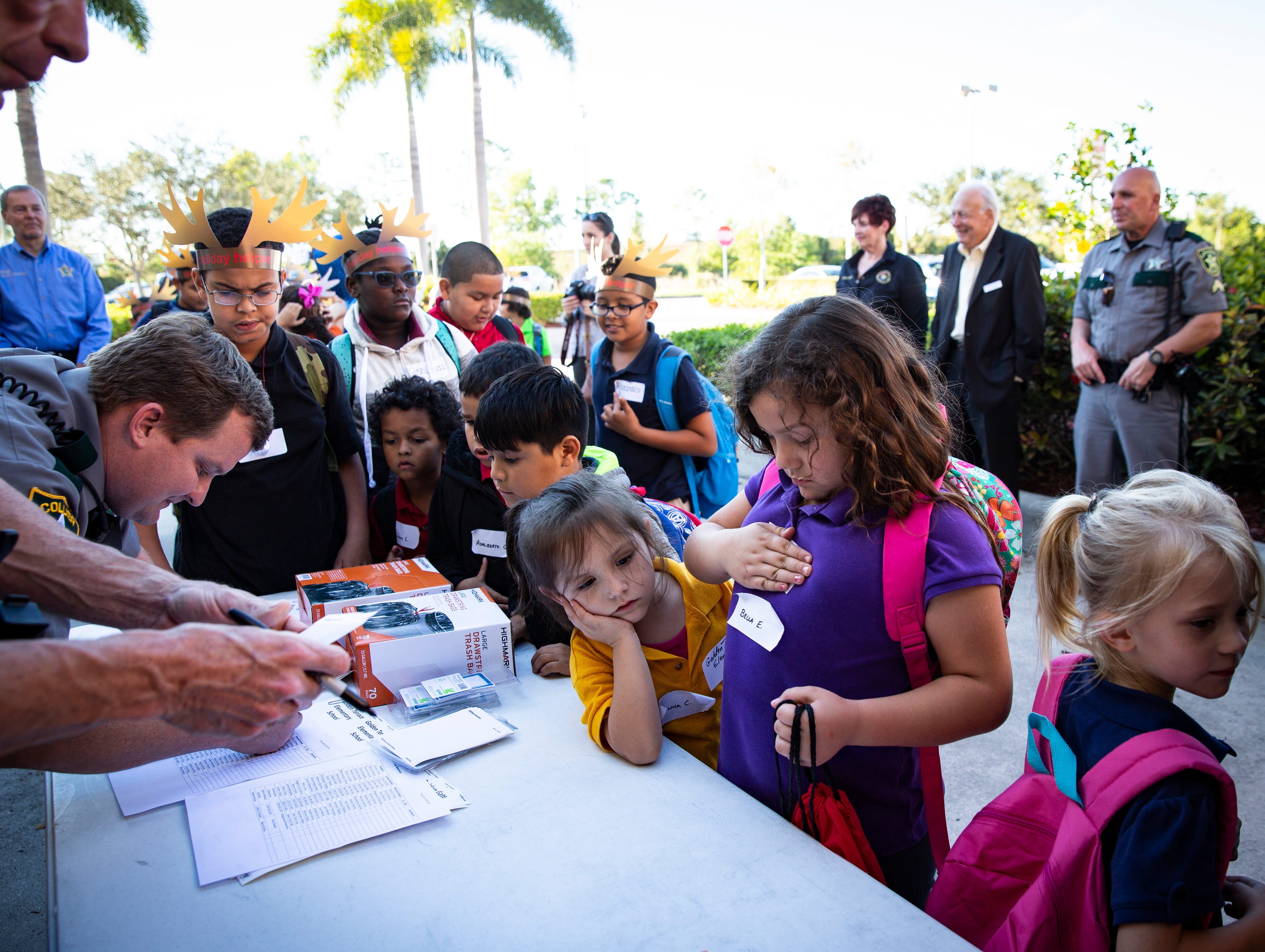 Children from four schools around the community, wait in line to get their name tags before heading to shop during the ÒShop With a SheriffÓ event at Target in North Naples on Tuesday, December 18, 2018. The Jewish Federation of Greater Naples partnered with the Collier County SheriffÕs Office for the fourth year in a row to help 78 children and their families during the holiday season.