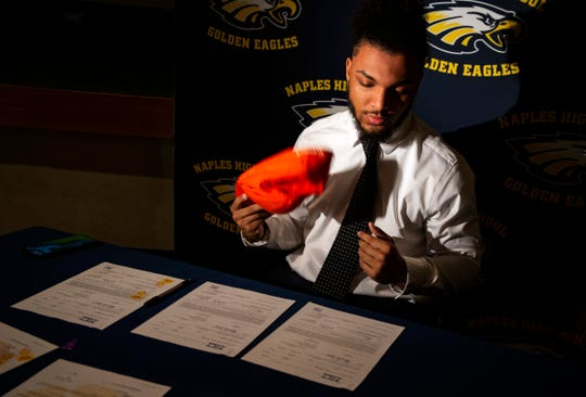 Naples High School running back Chez Mellusi looks over at the signed National Letter of Intent for Clemson University in South Carolina on Wednesday during the early signing period.
