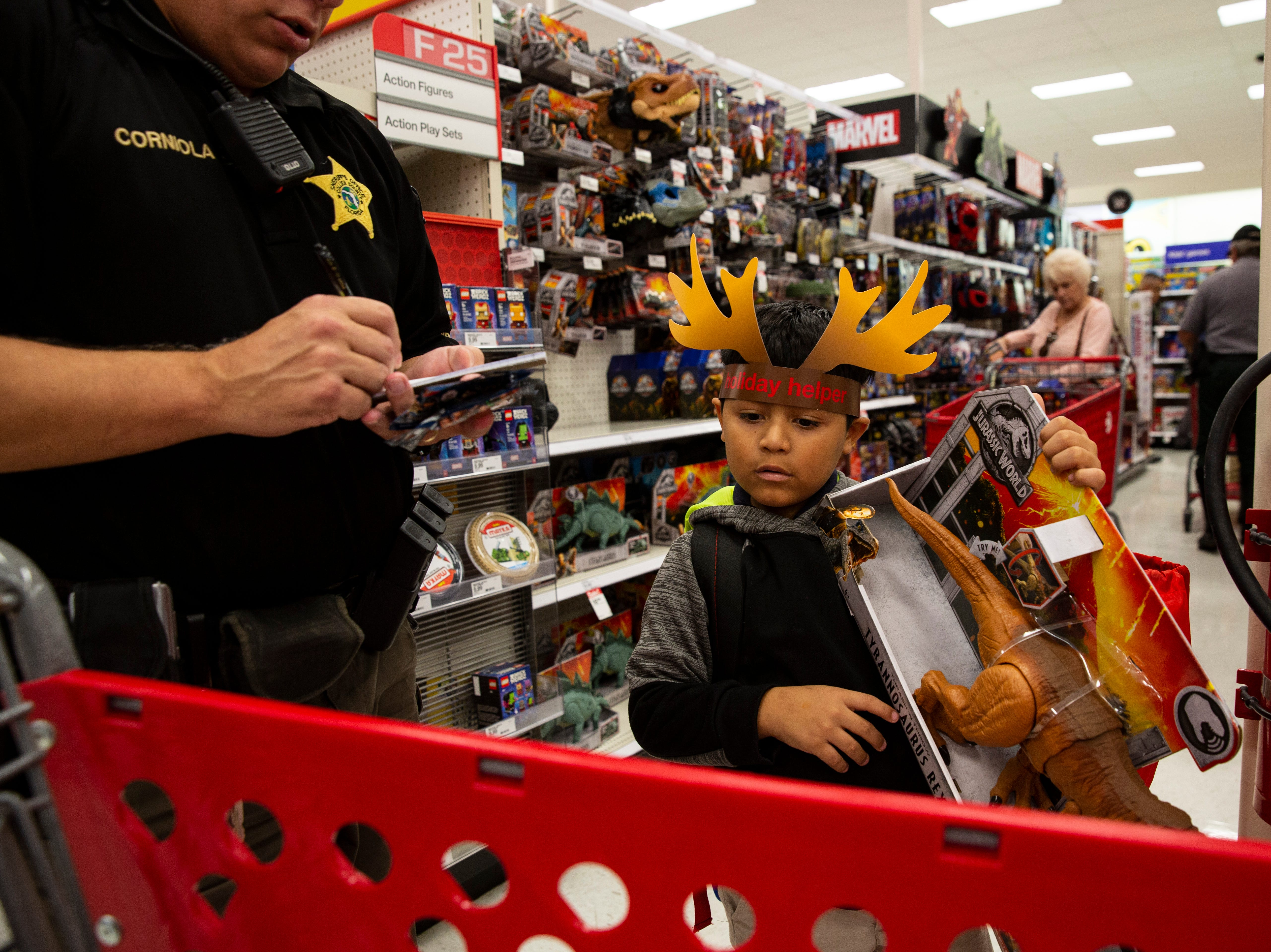 Roy Pineda tries to decide if he can purchase the Jurassic World T-Rex during the ÒShop With a SheriffÓ event at Target in North Naples on Tuesday, December 18, 2018. The Jewish Federation of Greater Naples partnered with the Collier County SheriffÕs Office for the fourth year in a row to help 78 children and their families during the holiday season.