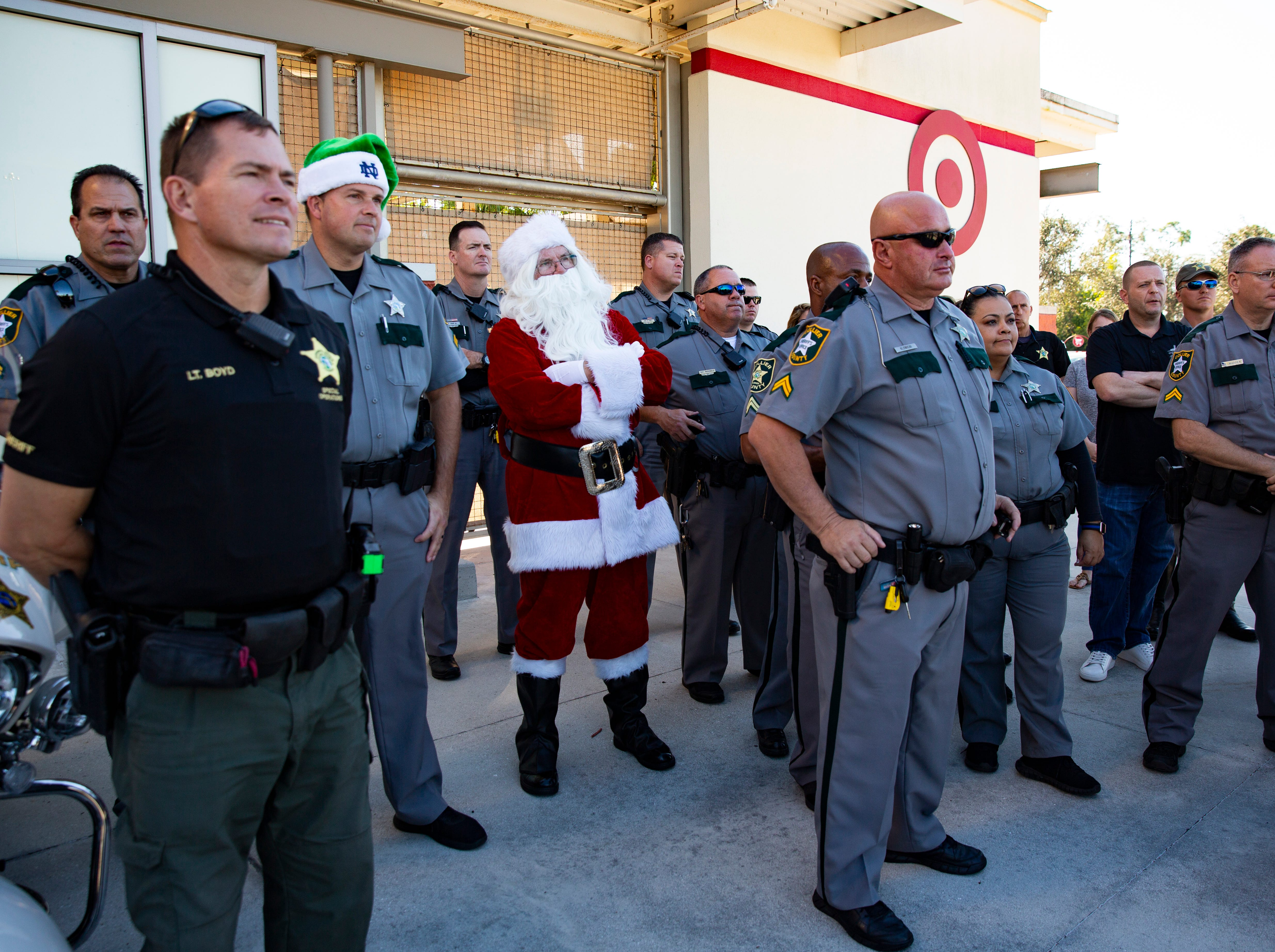 Santa Clause stands among the officers from the Collier County SheriffÕs Office as they wait for the children to arrive during the ÒShop With a SheriffÓ event at Target in North Naples on Tuesday, December 18, 2018. The Jewish Federation of Greater Naples partnered with the Collier County SheriffÕs Office for the fourth year in a row to help 78 children and their families during the holiday season.