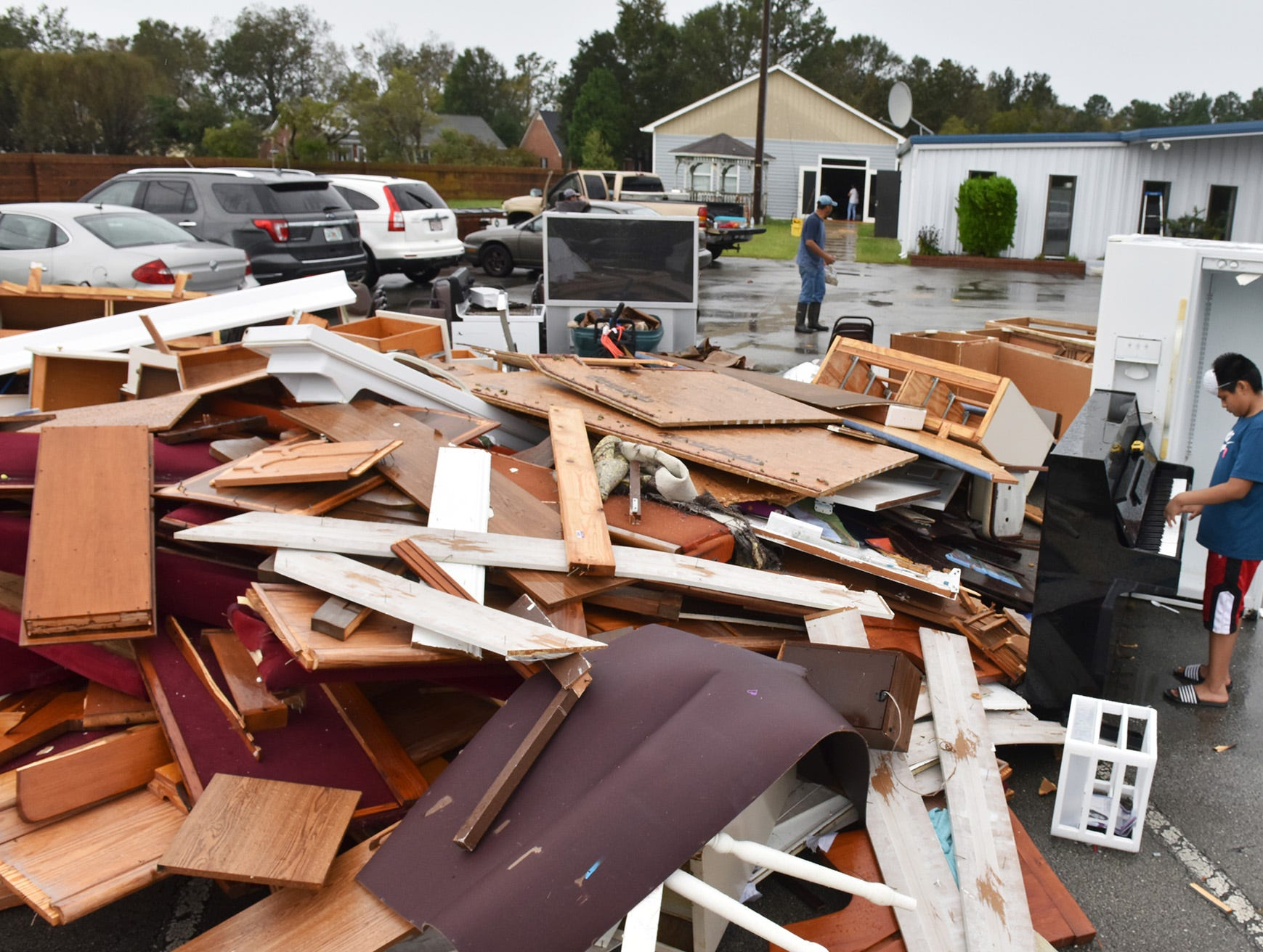 Manuel Osirio, 12, of Moorehead City, N.C. plays a piano among the pile of water soaked items being thrown out at the Seventh-Day Adventist Church in New Bern, N.C. on Sunday morning on September 16, 2018. Hurricane Florence brought heavy rains and winds to the area causing severe damage.