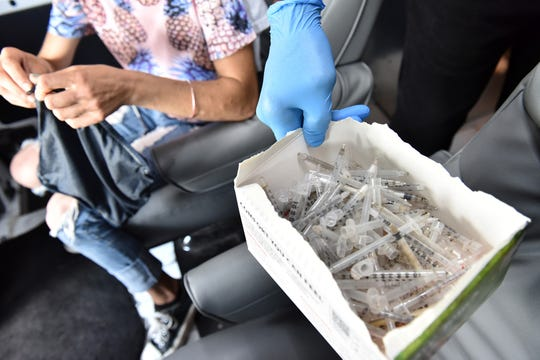 A client drops used syringes into a box to be exchanged, a total of 126 syringes were exchanged. The client said that they were mostly found on the ground in Paterson. A van parked in the Walgreen's parking lot provides clean needles in exchange for dirty ones twice a week in Paterson on Friday July 27, 2018. For every used syringe brought in, the harm reduction specialists with Hyacinth Foundation provides a new sterile syringe. The van is stocked with syringes of different sizes, alcohol wipes, constriction bands, cooking cups, water, strips to test for fentanyl, and other products to safely inject heroin.