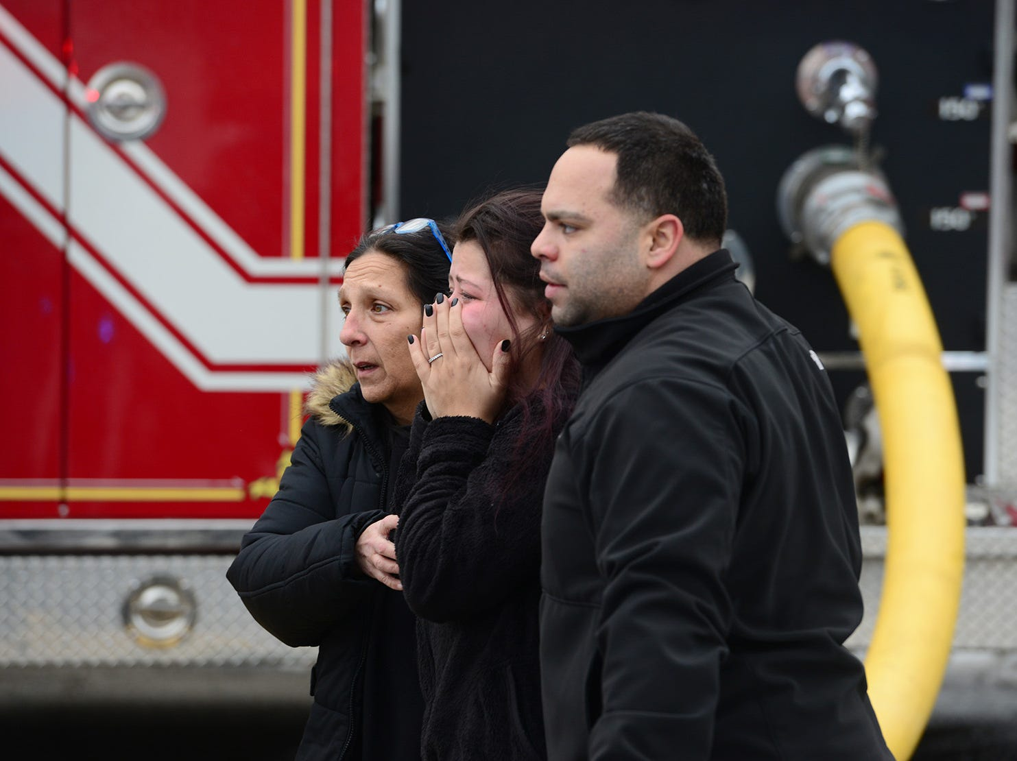 A victim is comforted as she walks away from the fire that gutted a home on Spruce Ave in Saddle Book on Monday February 19, 2018.