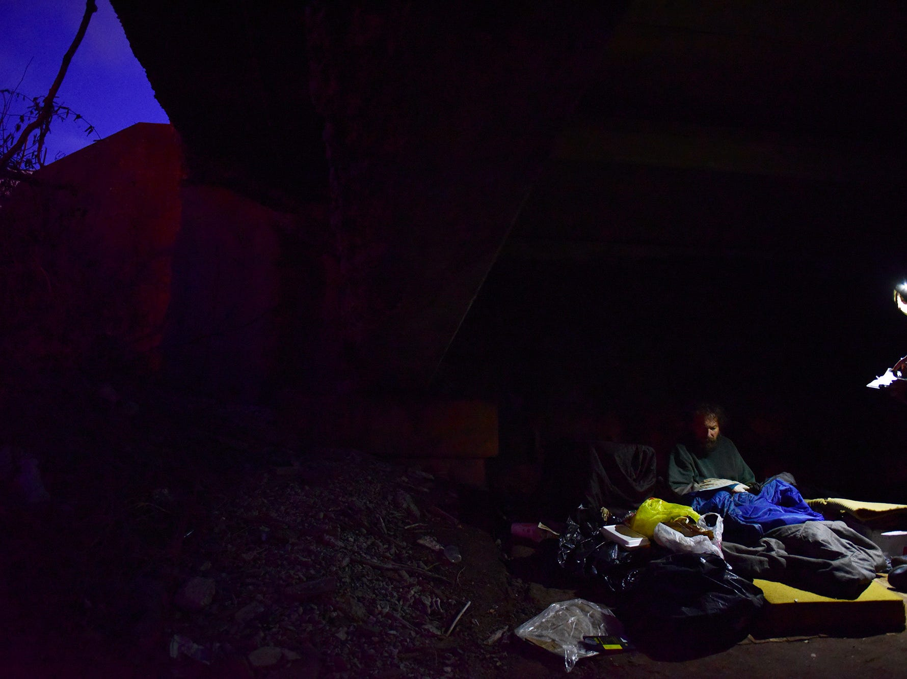 Volunteers for the annual Point in Time count of the homeless in Bergen County, talk to a homeless man sleeping under the Route 4 Bridge at the Hackensack River.