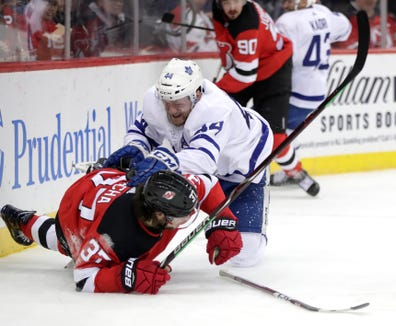 Toronto Maple Leafs defenseman Morgan Rielly, right, tries to regain his balance after losing his stick on a collision with New Jersey Devils center Pavel Zacha, of the Czech Republic, during the second period of an NHL hockey game, Tuesday, Dec. 18, 2018, in Newark, N.J.